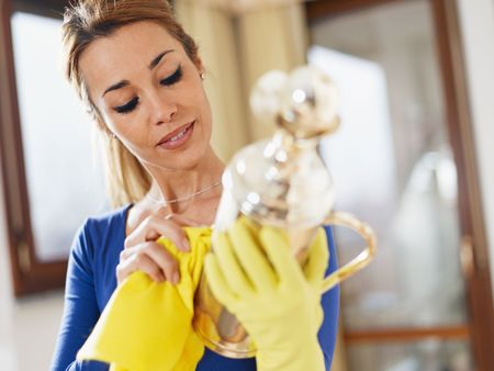 clean hand: portrait of woman with yellow gloves rubbing silver object. Horizontal forma