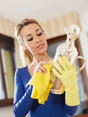 cubiertos de plata: Retrato de mujer con guantes amarillos frotando objeto de plata. Formato vertical