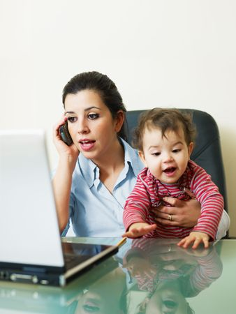 stressed business woman in office, holding her little girl while talking on mobile phone. Vertical shape, Copy space photo