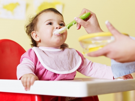 to feed: mom giving homogenized food to her daughter on high chair. Horizontal shape