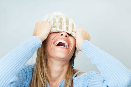 portrait of young woman laughing while covering face with wool hat. Horizontal shape, Copy space Stock Photo