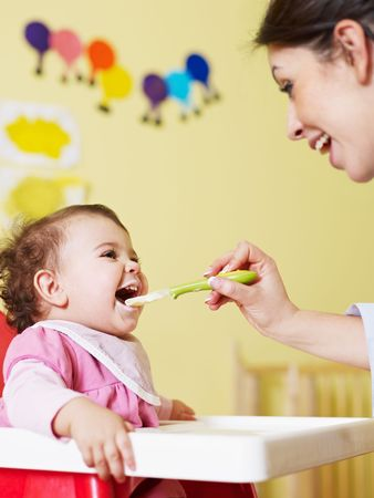 mom giving homogenized food to her daughter on high chair. Vertical shape photo