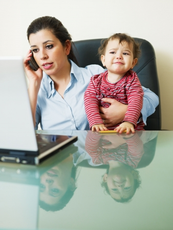stressed business woman in office, holding her little girl while talking on mobile phone. Vertical shape photo