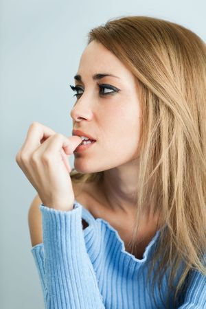 portrait of 30 years old woman biting her fingernails on cyan background. Vertical shape photo