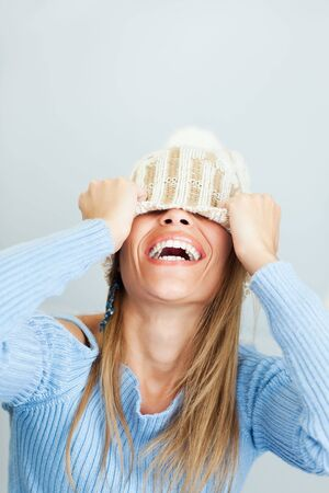 portrait of young woman laughing while covering face with wool hat. Vertical shape, Copy space photo