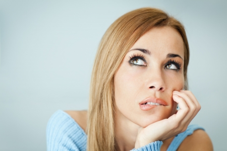 indecision: portrait of woman thinking and biting her lips, looking up with hand on cheek. Horizontal shape, Copy space