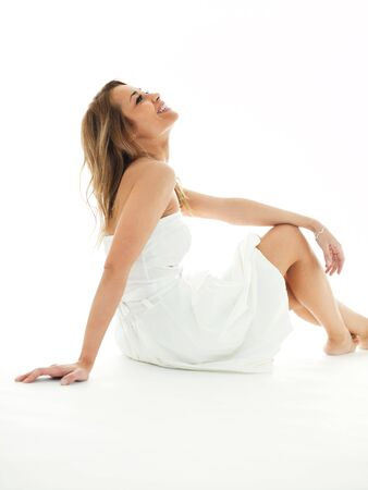 mid adult woman in white dress, looking up and smiling on white background. Vertical shape, copy space Stock Photo - 6550567