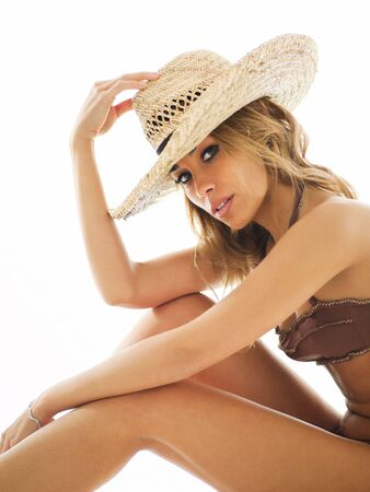 attractive mid adult woman in swim wear, holding straw hat and looking at camera on white background. Vertical shape Stock Photo - 6550569