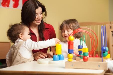 maestra jardinera: chica femenina de ni�o y 2-3 a�os jugando con juguetes de bloques en el jard�n de infantes. Forma horizontal