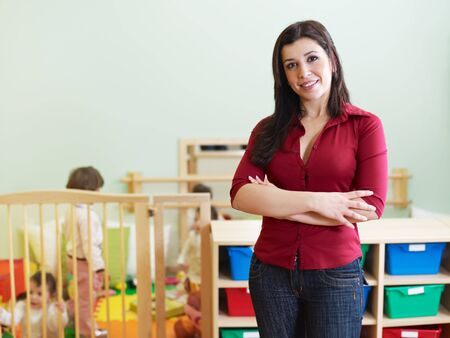 kindergarten teacher: portrait of mid adult teacher in kindergarten. Little girls playing with toys in background. Horizontal shape, copy space Stock Photo