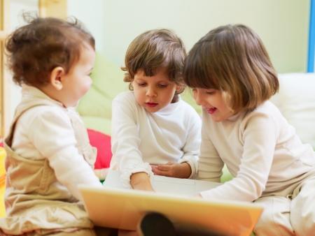 ni�as jugando: mujeres peque�o y 2-3 a�os edad ni�as jugando con el pc en el jard�n de infantes y sonriente. Forma horizontal Foto de archivo