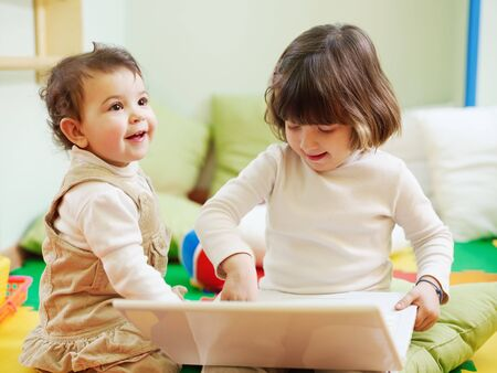 female toddler and 2-3 years old girl playing with pc in kindergarten. Horizontal shape photo