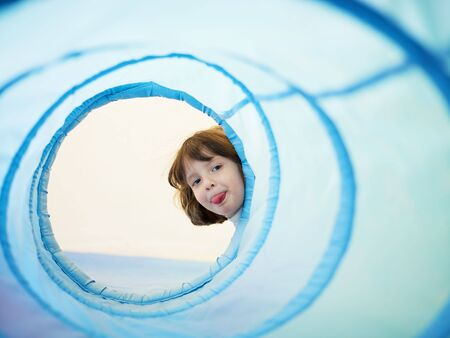2-3 years old girl peeking from blue toy tunnel and grimacing. Horizontal shape, Copy space photo