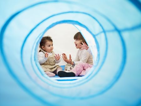 female toddler and 2-3 years old girls viewed from blue toy tunnel, clapping hands and singing. Horizontal shape, Copy space photo