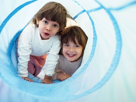 indoors: two 2-3 years old girls peeking from blue toy tunnel. Horizontal shape, Copy space