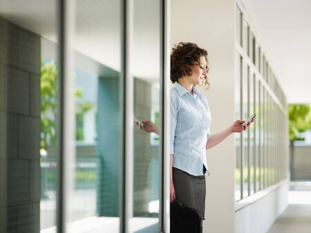 woman standing out of office building and reading emails on mobile phone. Horizontal shape, Copy space Stock Photo - 6877714