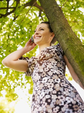 potrait of mid adult italian woman leaning on tree at sunset and talking on mobile phone. Low angle view, vertical shape. photo