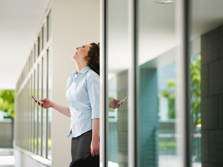 italian business woman standing out of office building and reading emails on mobile phone. Horizontal shape, Copy space photo