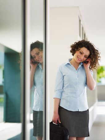 italian business woman talking on mobile phone outdoors and smiling. Vertical shape, copy space Stock Photo - 6877720