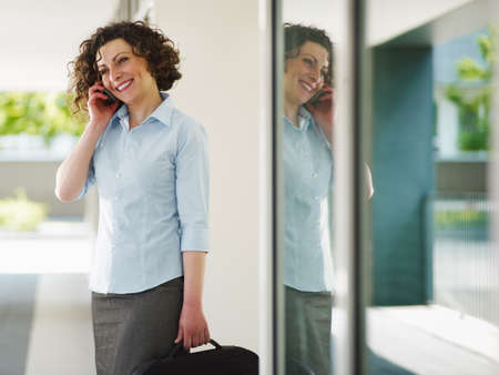 italian business woman talking on mobile phone outdoors and smiling. Horizontal shape photo