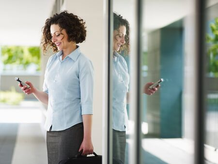 woman standing out of office building and reading emails on mobile phone. Horizontal shape, Copy space photo
