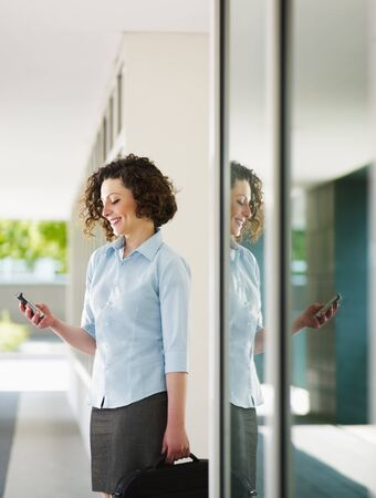 woman standing out of office building and reading emails on mobile phone. Vertical  shape, Copy space photo
