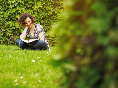 italian woman reading book on grass and smiling. Horizontal shape, copy space photo