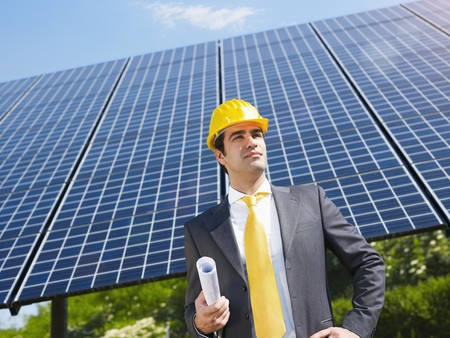 environmental issues: Portrait of mid adult italian male engineer holding blueprints in solar power station and looking up. Horizontal shape, front view. Copy space