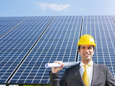Portrait of mid adult italian male engineer holding blueprints in solar power station and smiling at camera.Horizontal shape, front view. Copy space photo