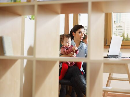 business woman in office, holding her little girl while talking on mobile phone. Viewed through library. Horizontal shape, full length photo