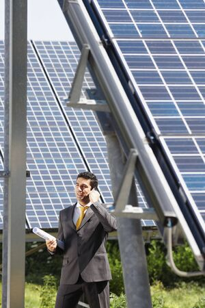 Portrait of mid adult italian male engineer holding blueprints in solar power station and talking on mobile phone. Vertical shape, side view. Copy space photo