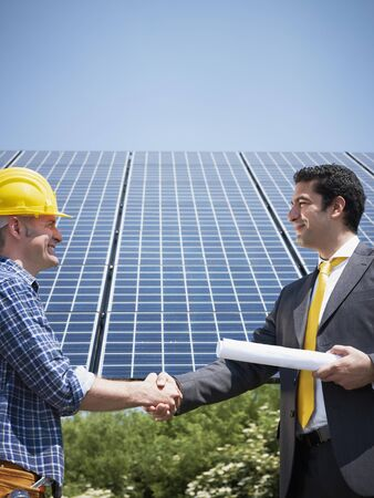 Portrait of mid adult italian male engineer holding blueprints and shaking hands to manual worker in solar power station. Vertical shape, side view. Copy space photo