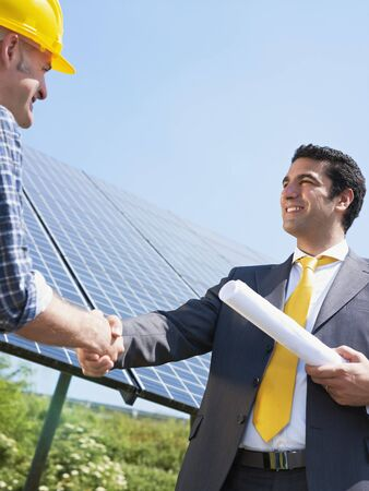 Portrait of mid adult italian male engineer holding blueprints and shaking hands to manual worker in solar power station. Vertical shape, low angle view. Copy space photo