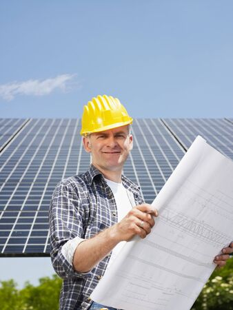Portrait of mid adult italian male electrician reading blueprints in solar power station and smiling. Vertical shape, side view. Copy space photo