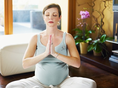 three quarter length: italian 6 months pregnant woman with hands clasped doing yoga exercise at home. Horizontal shape, three quarter length, front view