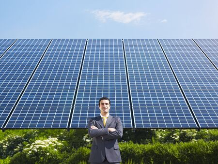 Portrait of mid adult italian male engineer with arms folded in solar power station, smiling at camera.Horizontal shape, front view. Copy space photo