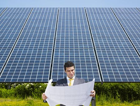 Portrait of mid adult italian male engineer reading blueprints in solar power station and smiling. Horizontal shape, front view. Copy space photo