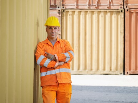 portrait of mid adult worker leaning on cargo container and looking at camera. Horizontal shape, front view, copy space photo