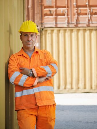 portrait of mid adult worker leaning on cargo container and looking at camera. Vertical shape, front view, copy space photo