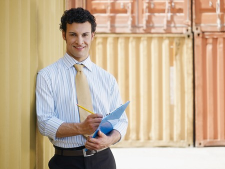 portrait of mid adult businessman leaning on cargo container and looking at camera. Horizontal shape, front view, copy space photo