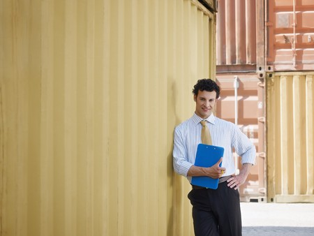 portrait of mid adult businessman leaning on cargo container and looking at camera. Horizontal shape, front view, copy space Stock Photo
