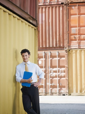 portrait of mid adult businessman leaning on cargo container and looking at camera. Vertical shape, front view, copy space photo