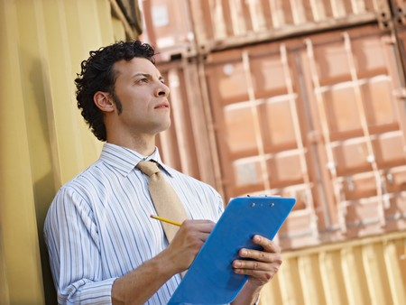 warehouse cargo: portrait of mid adult businessman leaning on cargo container and looking up. Horizontal shape, side view, copy space Stock Photo