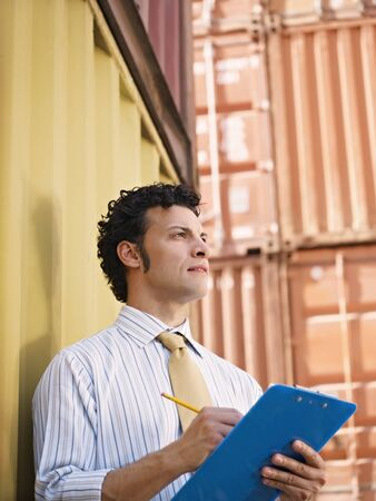 portrait of mid adult businessman leaning on cargo container and looking up. Vertical shape, side view, copy space photo