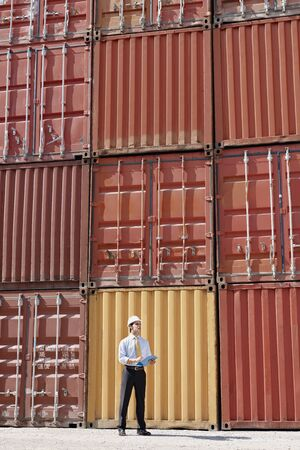 portrait of mid adult businessman standing near cargo containers and holding clipboard. Vertical shape, full length photo