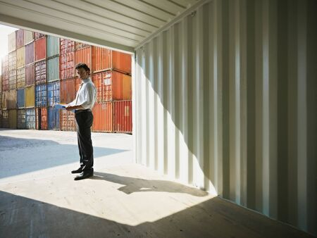 portrait of mid adult businessman standing inside cargo container and looking at camera. Horizontal shape, side view, copy space photo
