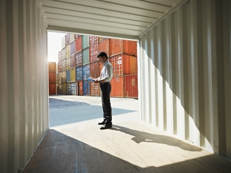 portrait of mid adult businessman standing near cargo container and writing on clipboard. Horizontal shape, side view, copy space photo