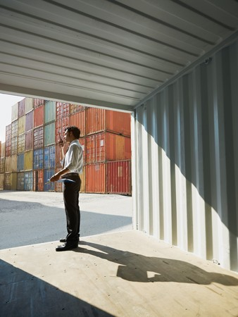 portrait of mid adult businessman standing near cargo container and talking . Vertical shape, side view, copy space photo