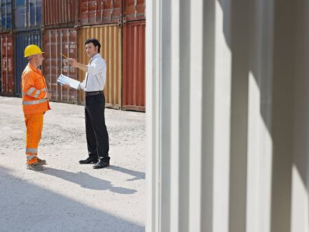 mid adult businessman and manual worker standing near cargo containers. Horizontal shape, full length, copy space photo