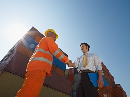 Mid adult businessman holding clipboard and shaking hands to manual worker near cargo containers. Horizontal shape, low angle view. Copy space photo